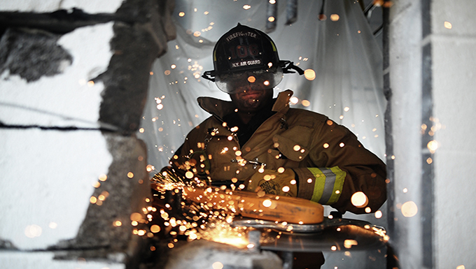 A firefighter with the 106th Rescue Wing, operates a powered saw in orde